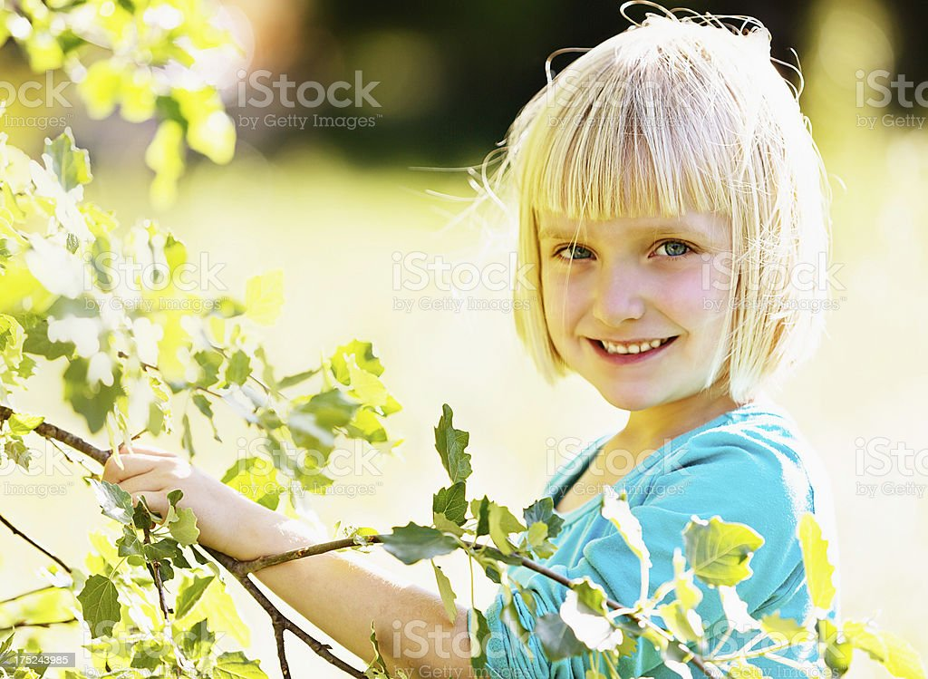 Pretty blonde pre-schooler smiles next to springtime leaves stock photo