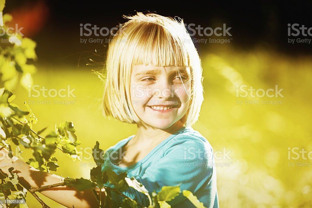 Pretty blonde pre-schooler smiling outdoors in hazy sunshine stock photo
