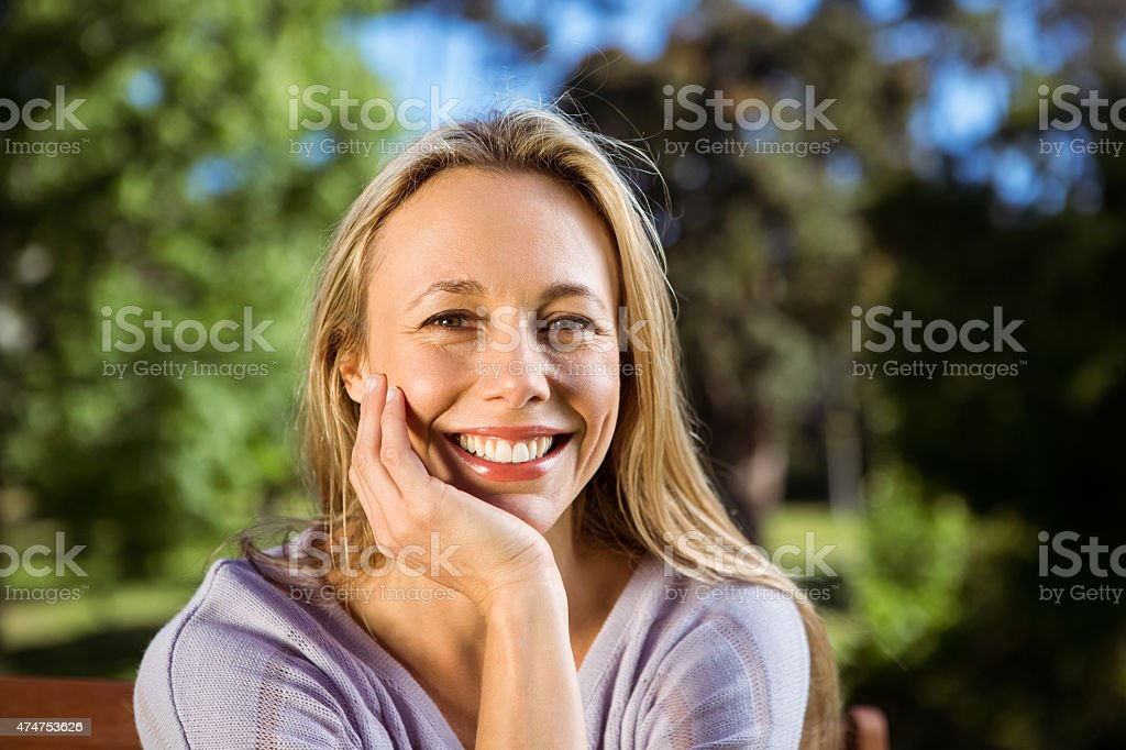 Pretty blonde relaxing in the park stock photo