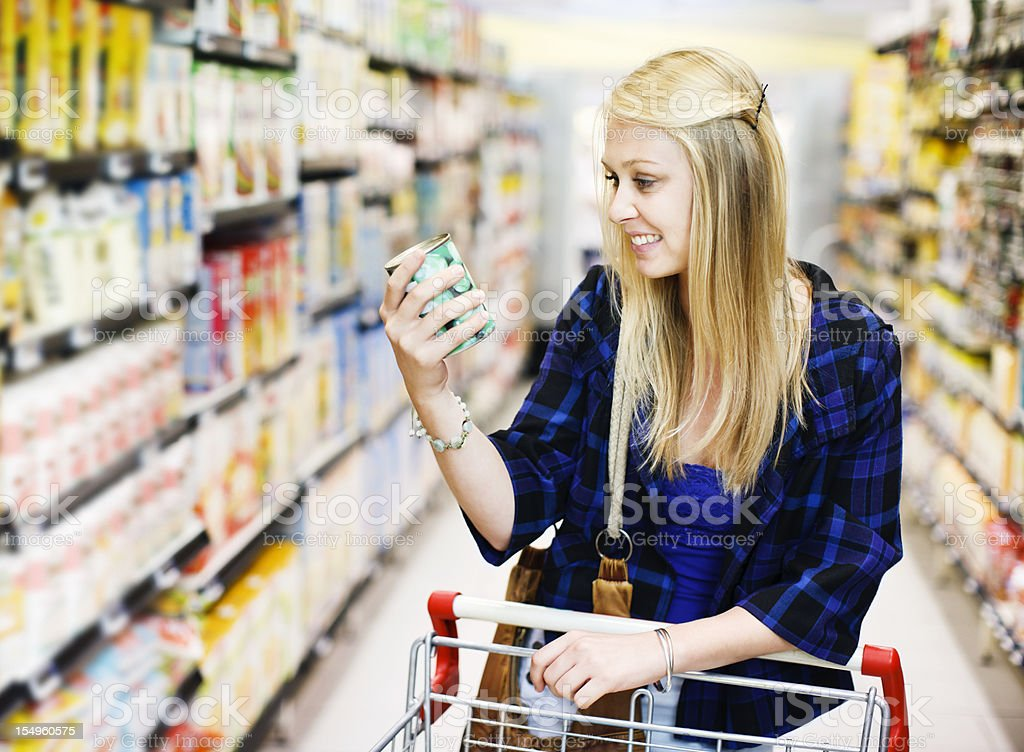 Pretty blonde shopper choosing canned peas in supermarket stock photo