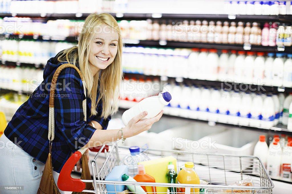 Pretty blonde shopper smilingly chooses milk from supermarket fridge royalty-free stock photo