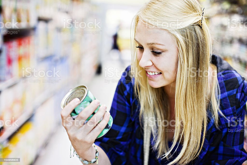 Pretty blonde smilingly checking canned goods in supermarket royalty-free stock photo