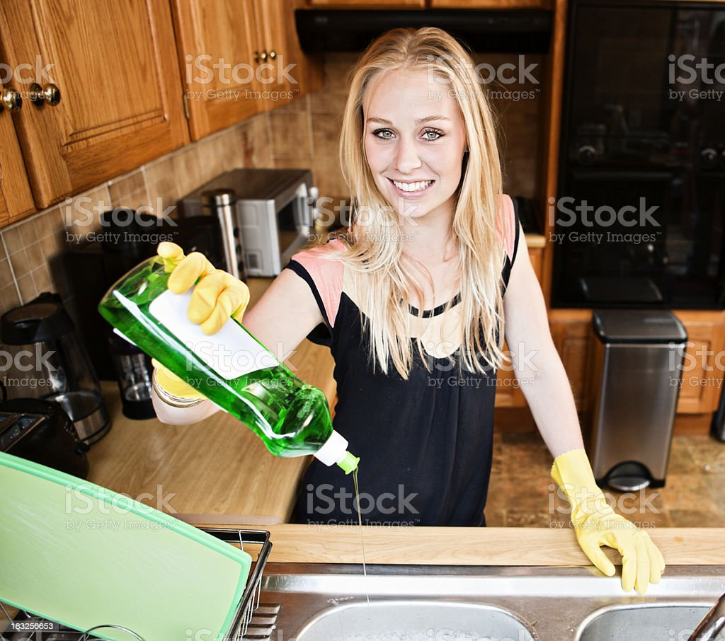 Pretty blonde smilingly pours dishwashing detergent in domestic kitchen stock photo