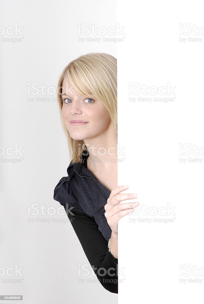 pretty blonde with blue eyes looking from behind an ad royalty-free stock photo