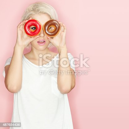 692840848istockphoto Pretty blonde  with multi-colored donuts 487654436