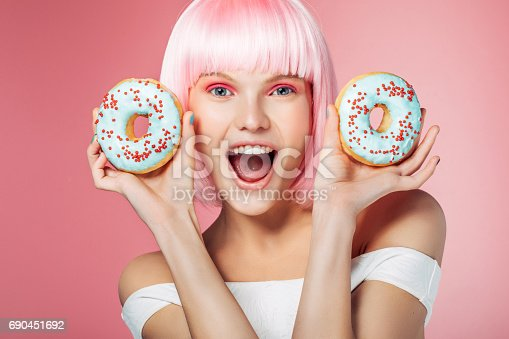 692840848istockphoto Pretty blonde with multi-colored donuts 690451692