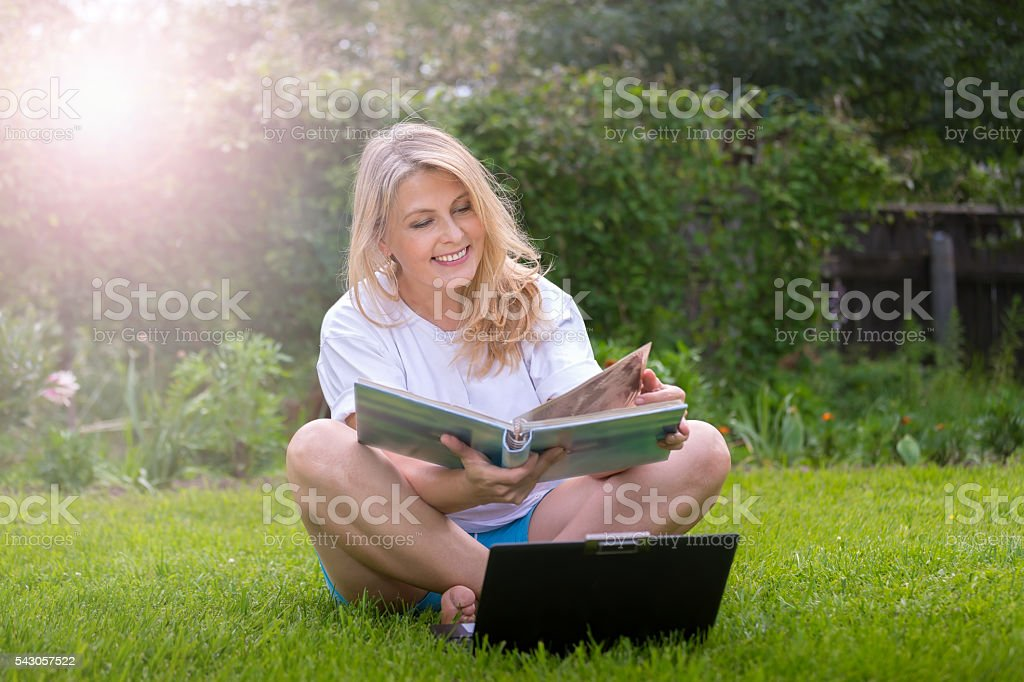 Pretty blonde with notebook on the grass royalty-free stock photo