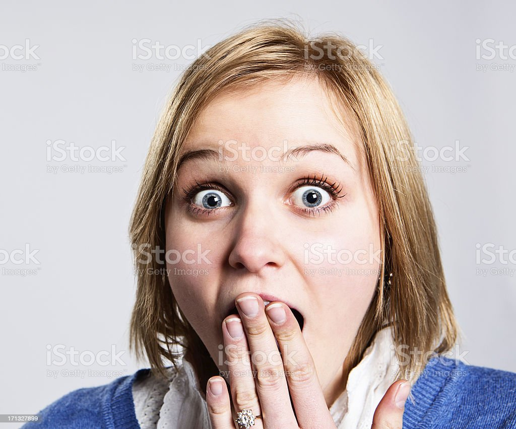 Pretty blonde with raised eyebrows, hand to mouth, amazed royalty-free stock photo