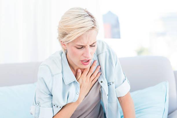 pretty blonde woman having breath difficulties - astmatisk bildbanksfoton och bilder