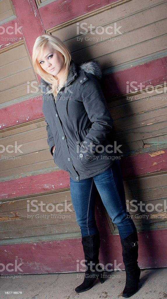 Pretty blonde woman standing against a wall royalty-free stock photo