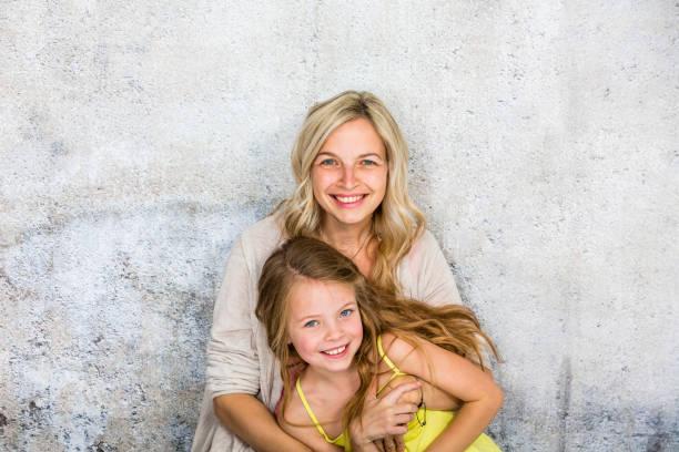 hübsche, blonde junge Mutter posiert und kuschelt mit ihrer Tochter vor einer Betonwand und hat viel Spaß – Foto
