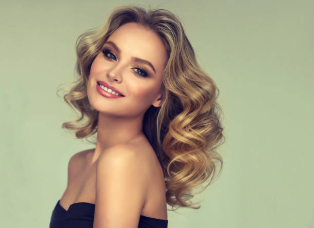 Pretty blond-haired model with curly, loose hairstyle and attractive makeup. stock photo