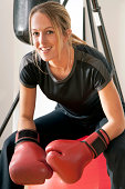 Pretty boxer smiling, sitting on a yoga ball with boxing gloves and punching bag in background