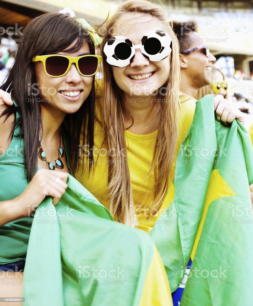 Pretty Brazilian football fans holding national flag stock photo