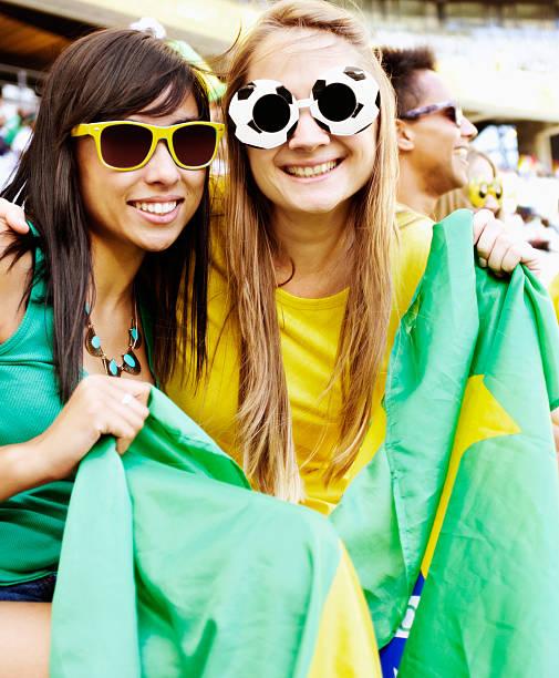 hübsche brasilianische fußballfans holding-flagge - spielerfrauen stock-fotos und bilder