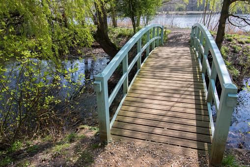 Pretty bridge over stream. Picturesque  country landscape. Painted wooden footbridge