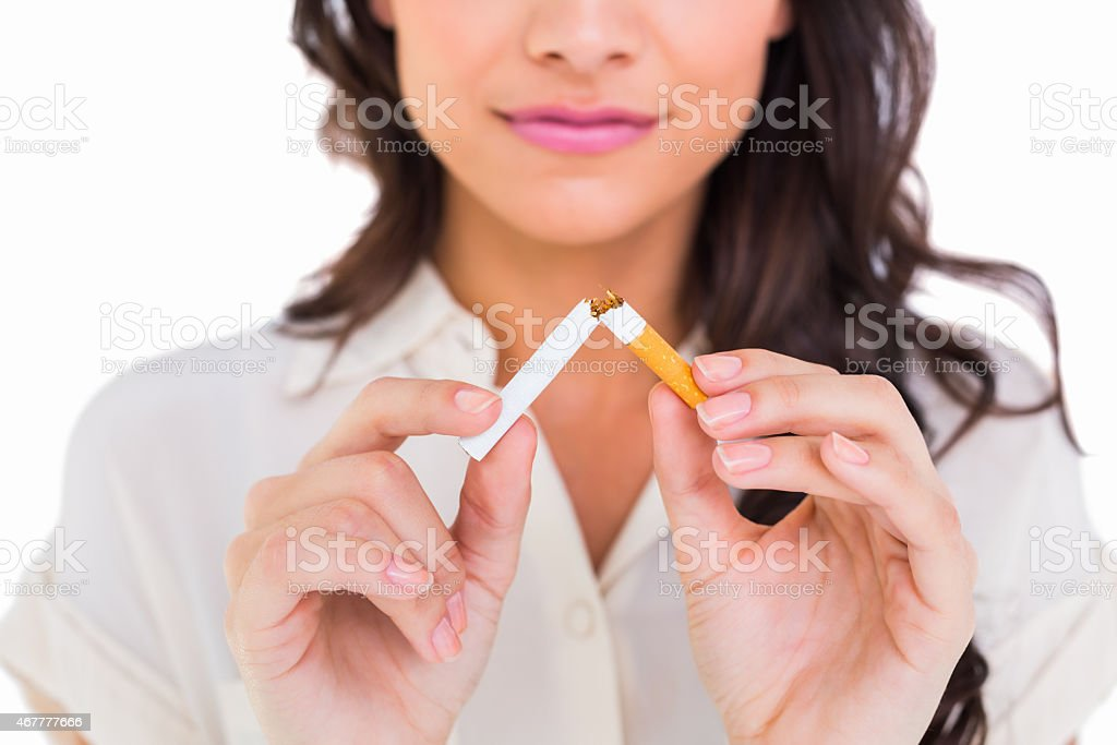 Pretty brunette breaking a cigarette stock photo