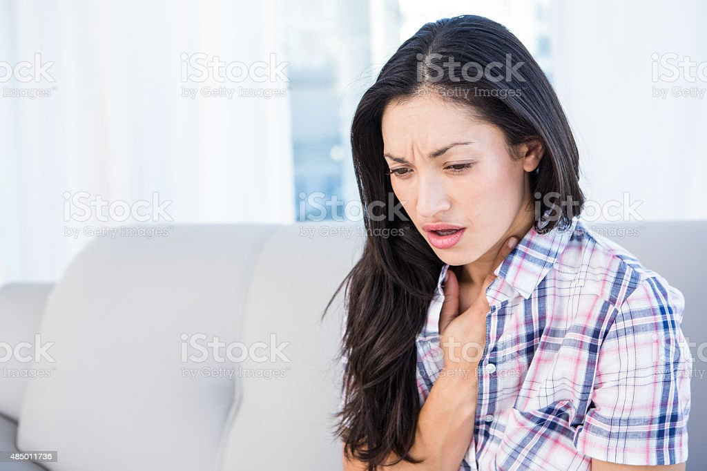 Pretty brunette coughing on couch stock photo
