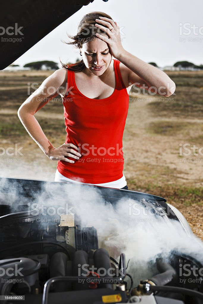 Pretty brunette desperate after car breakdown in a deserted area royalty-free stock photo