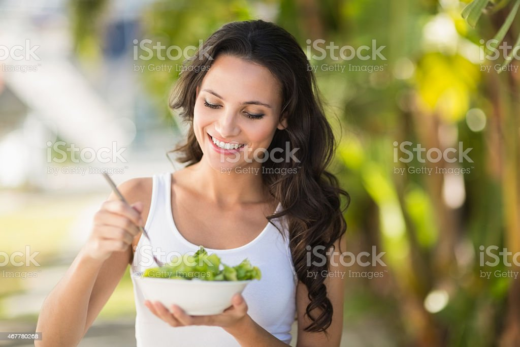 Pretty brunette eating bowl of salad stock photo