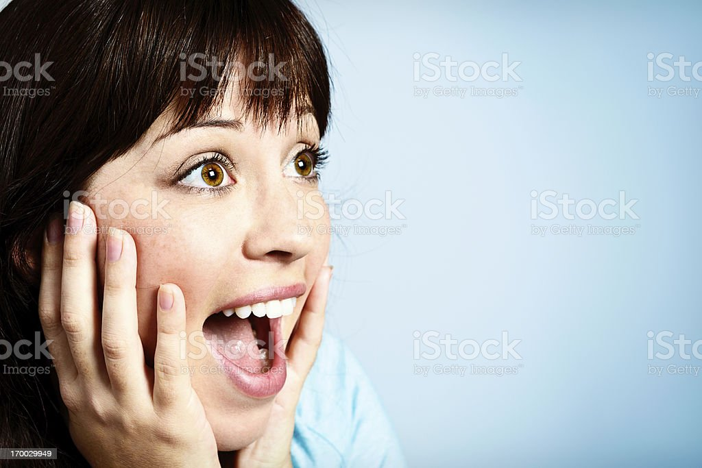 Pretty brunette gasping in happy surprise, hands to her face stock photo