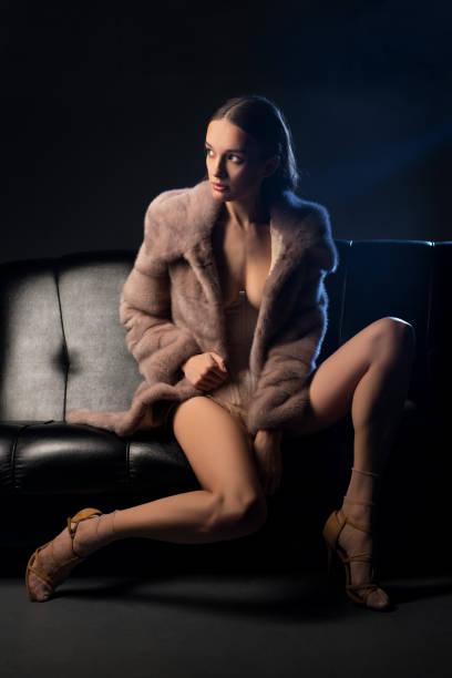 Hübsche Brünette im Pelzmantel auf einem Sofa in der Dunkelheit – Foto