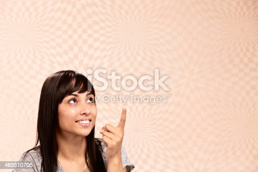 A sweet-looking young woman with long, dark hair points upwards, smiling, indicating copy space on the out-of-focus, psychedelically-patterned background.