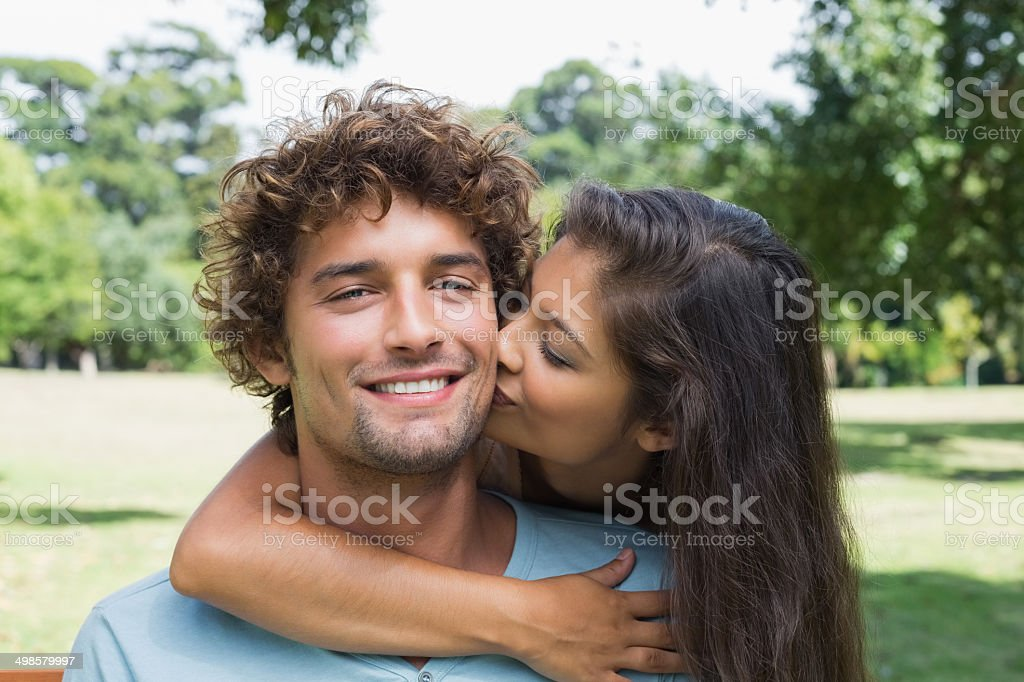 Pretty brunette kissing her boyfriend on the cheek stock photo