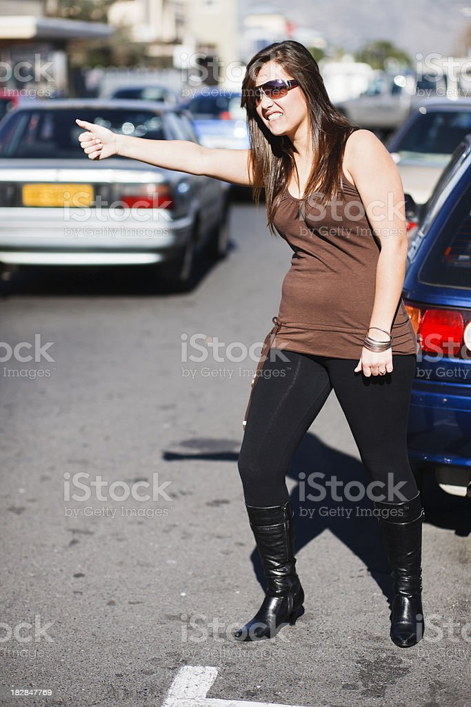 Pretty brunette looks distressed trying to hitch a ride royalty-free stock photo