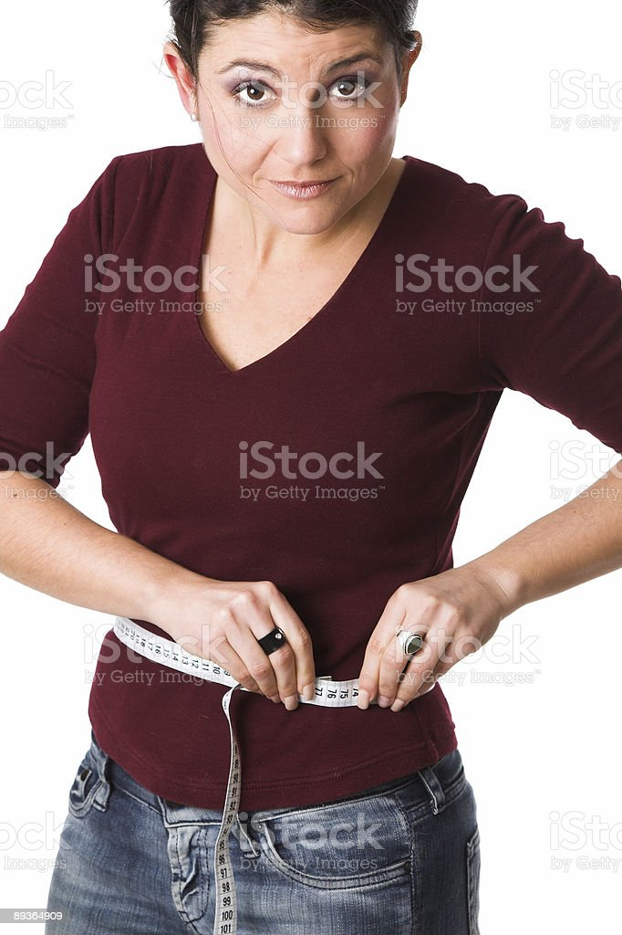 Pretty brunette measuring herself royalty-free stock photo
