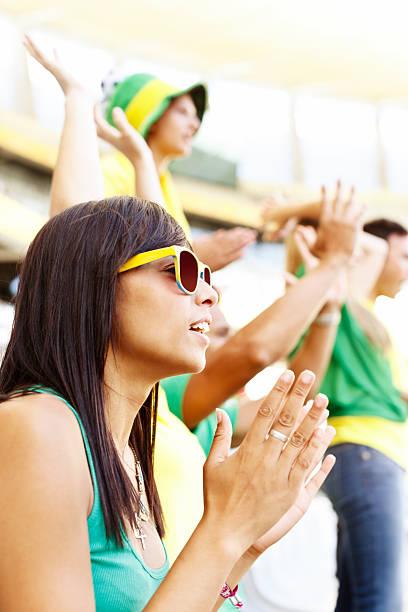 ziemlich brunette fußball-fan oder wag applaudieren ihr team - spielerfrauen stock-fotos und bilder