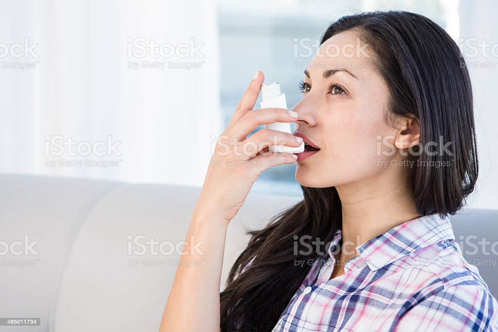 Pretty brunette using inhaler on couch stock photo