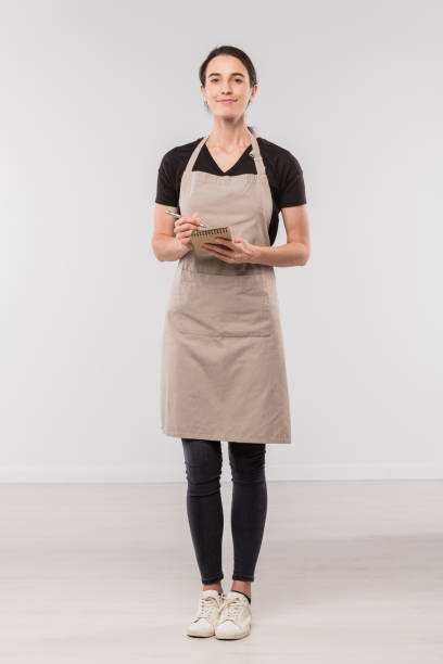 Pretty brunette waitress in workwear making notes in small notepad Pretty brunette waitress in workwear making notes in small notepad while standing in front of camera in isolation apron stock pictures, royalty-free photos & images