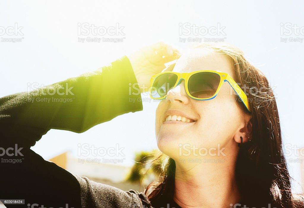 Pretty brunette wears sunglasses to shield against the fierce sunlight stock photo