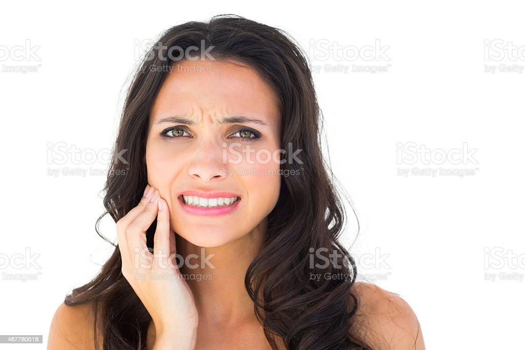 Pretty brunette with a toothache stock photo
