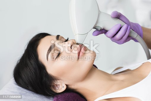 Pretty brunette woman getting hair removing on face. Procedure laser epilation at beauty studio