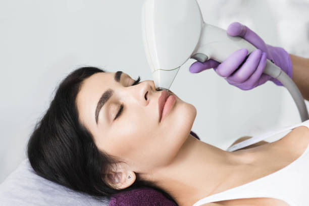Pretty brunette woman getting hair removing on face. Procedure laser epilation at beauty studio Pretty brunette woman getting hair removing on face. Procedure laser epilation at beauty studio laser stock pictures, royalty-free photos & images