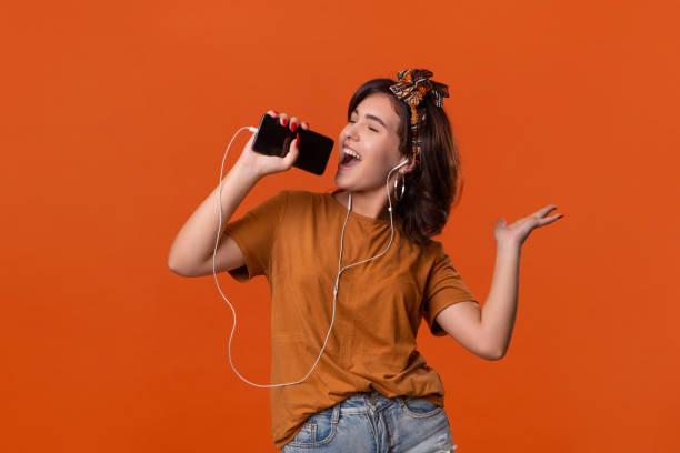 hübsche brünette frau in einem t-shirt und schöne stirnband tanzen hören musik mit kabelgebundenen kopfhörer über orange hintergrund isoliert. das leben genießen - mensch und maschine stock-fotos und bilder