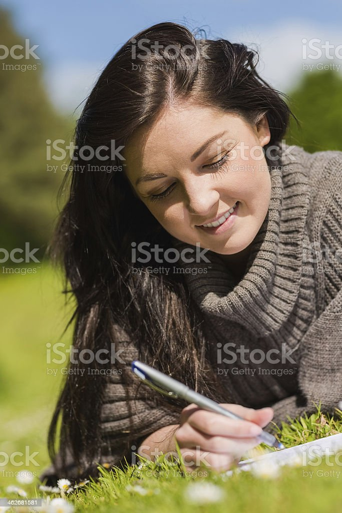 Pretty brunette writing while lying on the grass royalty-free stock photo