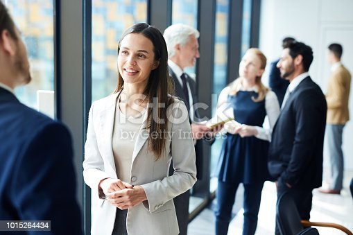 Smiling pretty young business lady in jacket talking to colleague and discussing business forum topics during break