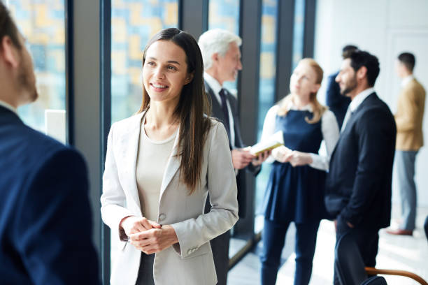 Pretty business lady talking to colleague Smiling pretty young business lady in jacket talking to colleague and discussing business forum topics during break event stock pictures, royalty-free photos & images