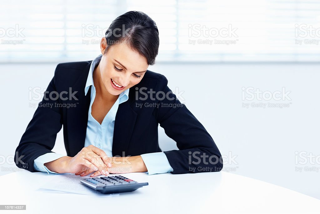 Pretty business woman using a calculator royalty-free stock photo