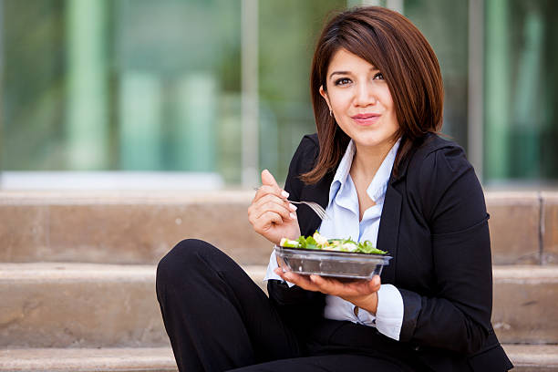 Pretty businesswoman eating healthy stock photo