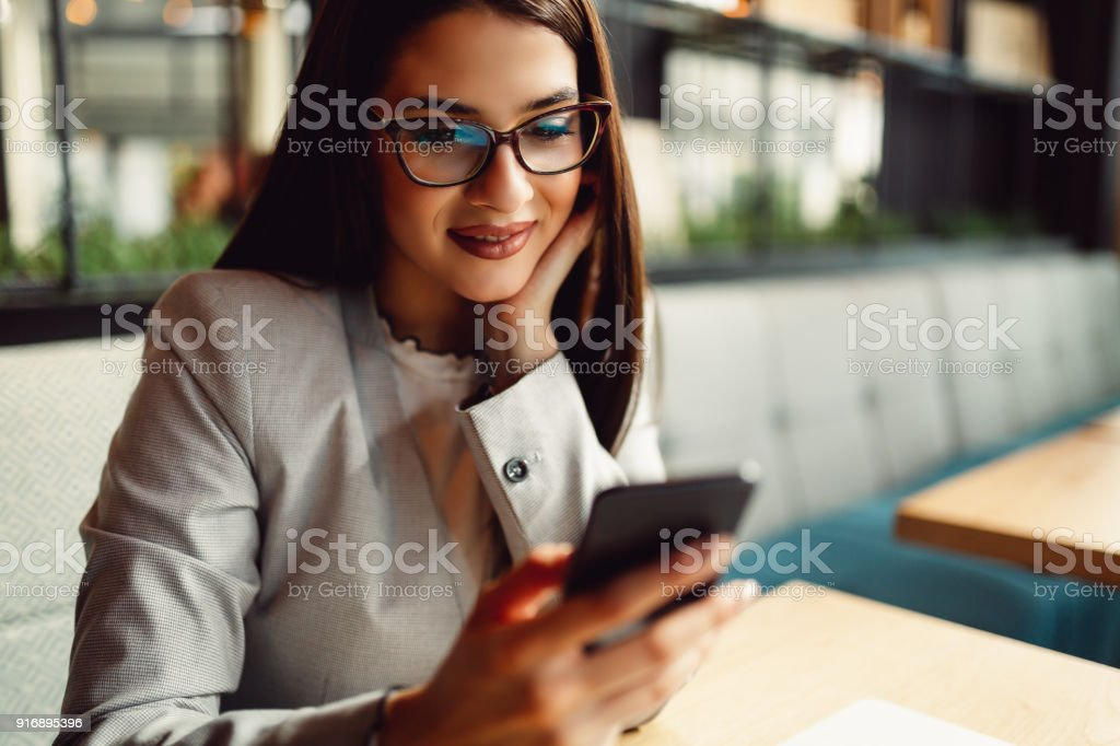 Pretty businesswoman holding a mobile phone. stock photo