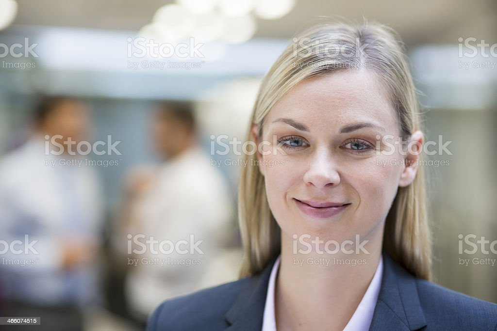 Pretty Businesswoman posing while colleagues talking together in background royalty-free stock photo