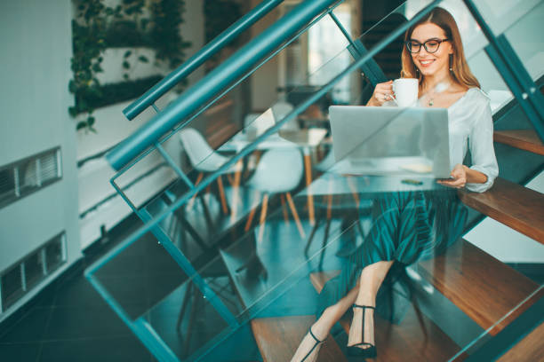 Pretty businesswoman sitting oh the office stairs , having coffee break and web-surfing internet stock photo