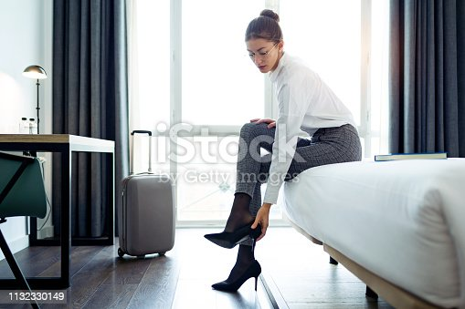 istock Pretty businesswoman taking off high heels shoes after work at her hotel room. 1132330149