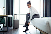 Shot of pretty businesswoman taking off high heels shoes after work at her hotel room.