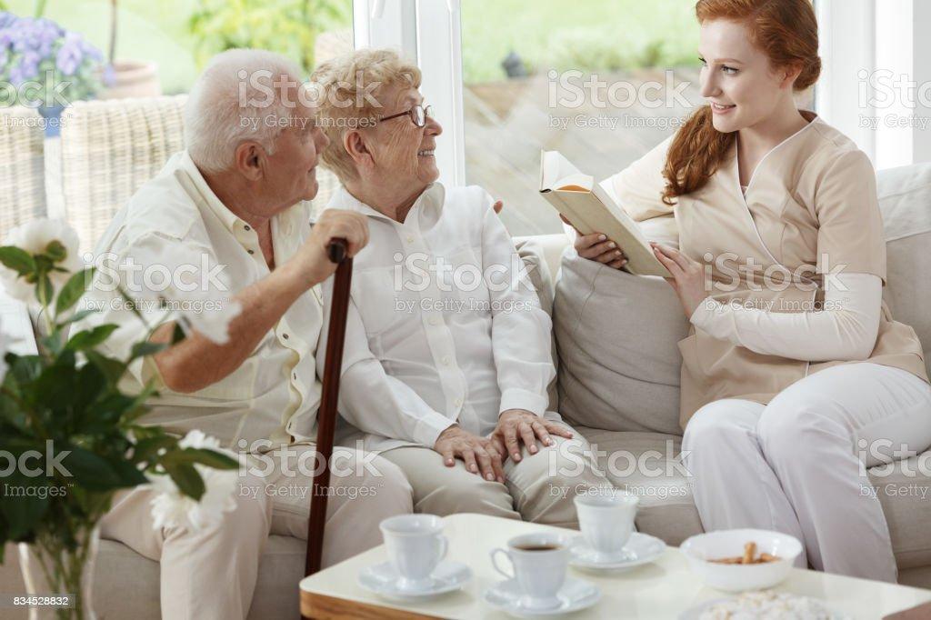 Pretty caregiver reads book stock photo