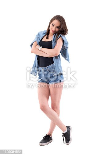 Pretty casual brunette in jeans shorts looking at camera sceptically. Full body isolated on white background.